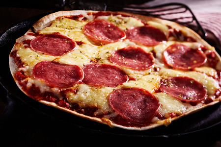 Spicy salami tortilla pizza on a thin flat bread base with melted cheese and tomato in a close up view