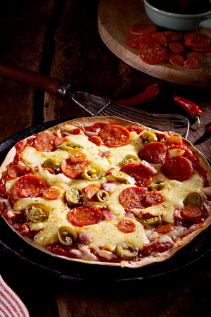 ovenbaked: Tasty spicy salami or chorizo pizza with olives on a crispy oven-baked masa tortilla served on a vintage plate in a rustic restaurant