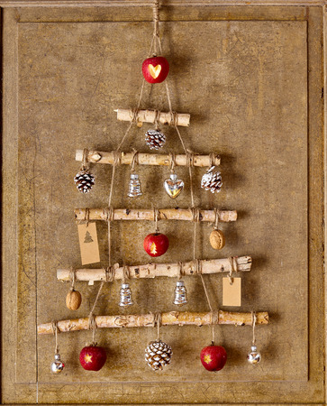 christamas: Christmas tree artwork made from natural objects connect by string and hanging from top of wooden board