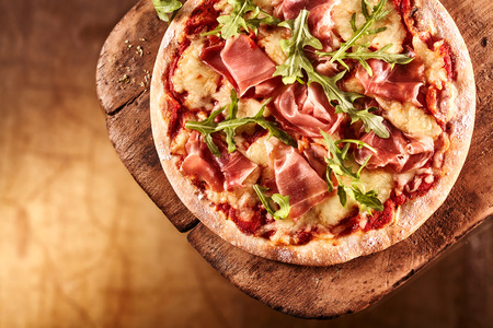 ambiente: Top down view on delicious single round pizza with arugula lettuce and bacon meat toppings