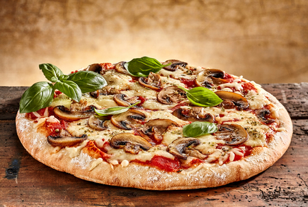 Close up on delicious freshly baked small pizza with melted cheese mushrooms and basil Banco de Imagens - 65412947