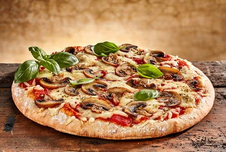 Zblízka na chutné čerstvě upečené malé pizzy s houbami strouhaným sýrem a bazalkou
