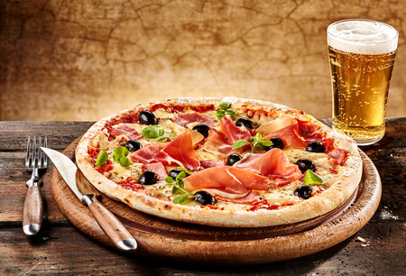 나이프와 포크 옆에 맥주와 함께 둥근 나무 접시에 베이컨 피자의 개인 서빙 스톡 콘텐츠