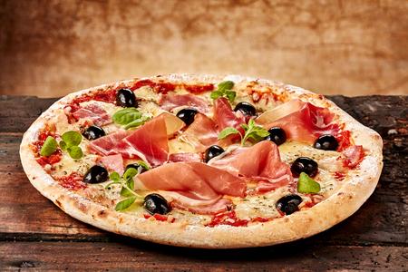 Close-up van enkele vers gebakken spek, kruiden, kaas en olijven kaas pizza op oude lijst