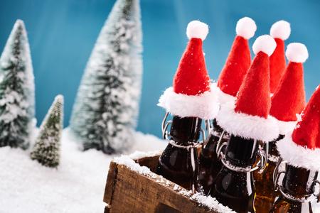 Smakelijke bierflessen voor de winterpartij in een bruine houten mand voor winters landschap Stockfoto