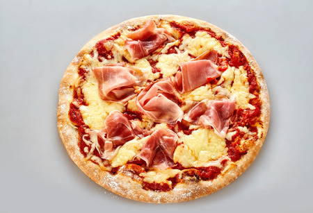 pizza base: Traditional Italian pizza with parma ham on a bed of tomato and melted mozzarella on a thick crusty pastry base, high angle view