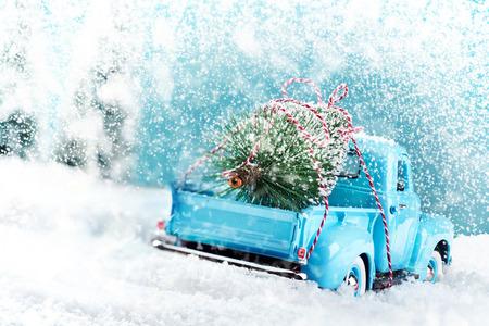 Campagna di neve con camion di albero di Natale che guida casa