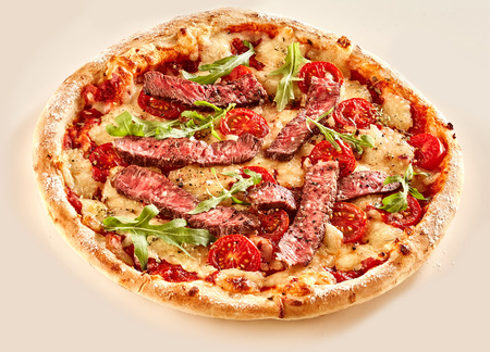 Freshly baked single serving of beef pizza with tomato and arugula greens as toppings Imagens - 65740521