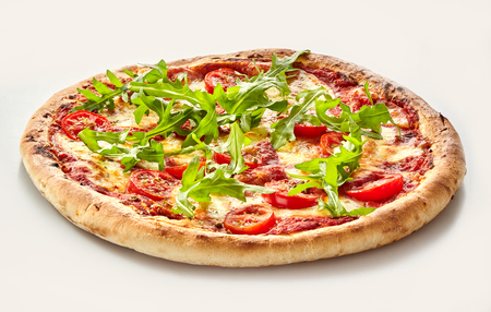 Fresh arugula or rocket Italian pizza with melted mozzarella and tomato on a thick oven baked crust Stock Photo