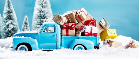 x mass: Christmas presents on blue truck falling from bed in the snow. For xmas concepts. Stock Photo