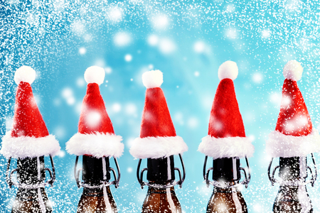 Row of brown beer bottles with colorful festive red Santa hats standing outdoors in falling snow against a cold blue winter sky with copy space for your Christmas greeting