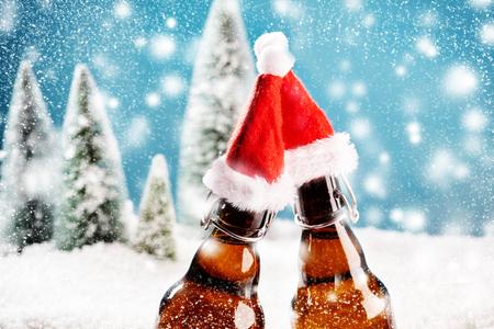 Twee glazen bierflesjes klinken samen. Een kaart voor de uitnodiging van de Kerstmispartij Stockfoto