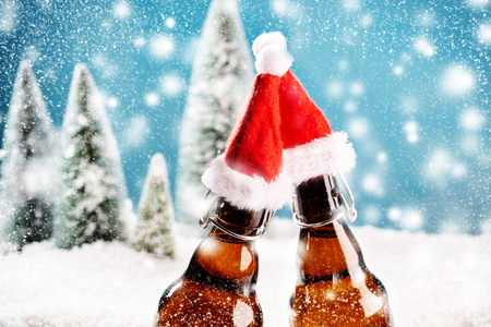 Two xmas beer bottles clink together. A card for christmas party invitation Фото со стока