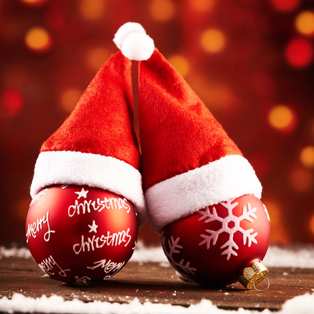 motivos navideños: Cozy pair of colorful red Christmas baubles with Santa hats and decorated motifs on a wooden table with snow against a background of warm sparkling party light bokeh Foto de archivo