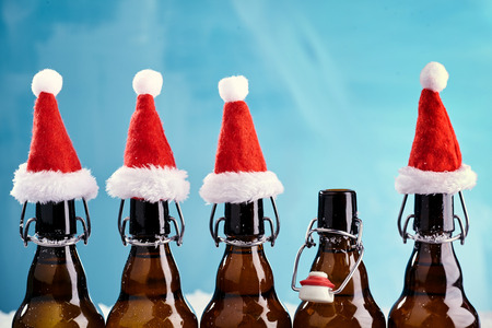 Winter beer bottle merry christmas party. Beer Bottles in a row with funny christmas hats for xams happenings