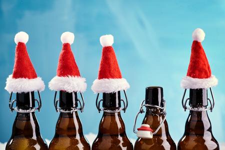Winterbierflasche Frohe Weihnachtsparty. Bierflaschen in einer Reihe mit lustigen Weihnachtshüten für xams Geschehen Standard-Bild