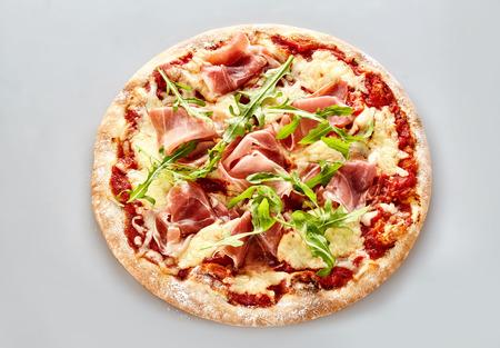 Délicieux pizza italienne avec jambon de parme et à la roquette sur le fromage de mozzarella fondue servi sur une croûte à tarte épaisse, vue à angle élevé sur gris clair