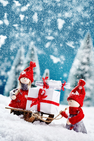 x mass: Cute christmas figures in the snow with wooden sled and white and red gifts with a bow on snowy landscape Stock Photo