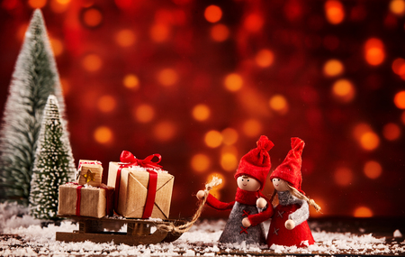 Two cute little Christmas figures with a sled full of gifts in a snowy winter landscape with colorful bokeh of warm toned lights and copy space