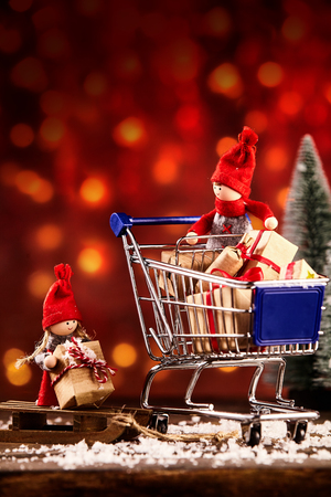 Two cute little red festive Christmas dolls out shopping on Xmas eve loading their wooden sled with gifts from a trolley against a warm red bokeh of party lights