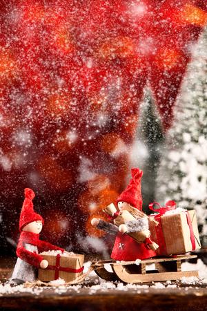Zwei süße kleine Weihnachtspuppen beim Einkaufen, die an einem verschneiten Wintertag ihren Holzschlitten mit Geschenken im Freien mit warmen roten festlichen Tönen beladen Standard-Bild