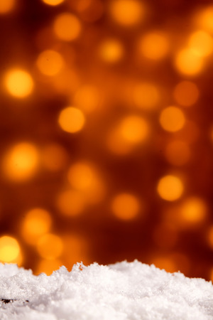 Festive Christmas background with copy space on sparkling orange party lights bokeh and selective focus to fresh white winter snow in the foreground Stock Photo