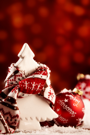 Cute white Christmas tree ornament in a woolly winter scarf standing in scattered snow alongside a red bauble with Merry Christmas greeting, muted red bokeh background with copy space Stock Photo