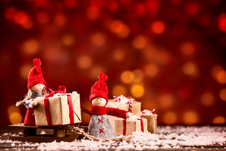Wooden figurines unload presents wrapped in gold paper onto the snow against a red background