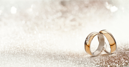 Panorámica de la bandera de alianzas de boda del oro dos en posición vertical simbólicos del amor y el romance en un fondo de brillo con textura con copia espacio para el saludo o felicitación Foto de archivo