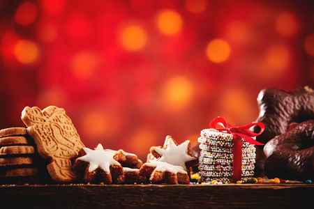 confections: Christmas cookies and biscuits festive background arranged on a rustic wooden table with spicy speculoos, starsand chocolate confections, low angle with colorful party bokeh and copy space Stock Photo