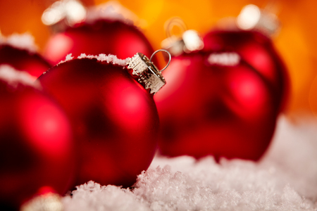 Festive red Christmas bauble background with a group of balls resting in fresh winter snow and selective focus to the second ornament