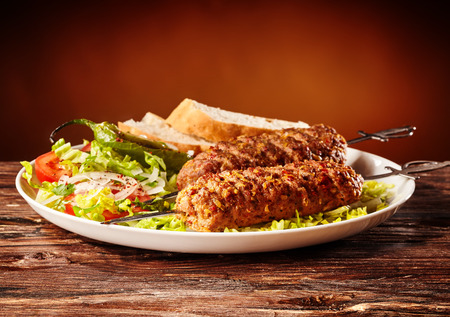 Adana kebabs made with young spicy minced lamb on long metal skewers with a fresh salad and bread for a delicious Turkish regional meal