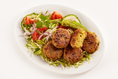 Overhead view of vegetarian chickpea patties set on a bed of lettuce in an oval plate against a white background Фото со стока