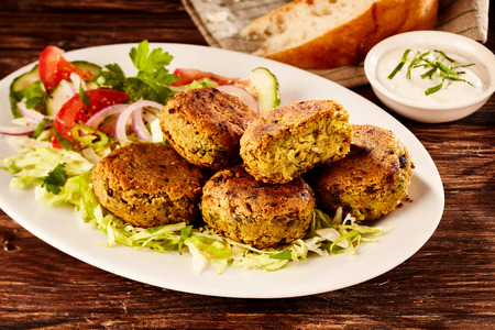 fava bean: Fried chickpea and fava bean patties, or falafel, served on a large platter with fresh salad and sour cream for tasty Turkish cuisine