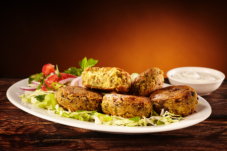 Plate of delicious small chickpea patties on a bed of lettuce beside cup of dipping sauce