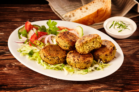 Serving of fried Turkish falafel patties and salad made from chickpeas or fava beans accompanied by a sour cream dip on a rustic wooden table