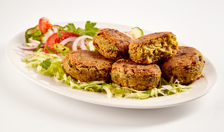 fava: Spicy fried felafel patties beside cut vegetables against a white background
