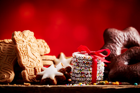 Close up on assorted gingerbread, graham cracker and wrapped in red bow chocolate Christmas cookies with copy space above Stock Photo