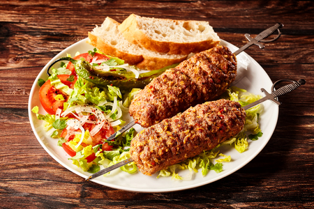 Delicious Turkish adana skewers or kebabs made from minced spicy young lamb roasted over oak served on a plate with fresh salad