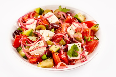 tomato slices: Small bowl of yummy olive and tomato salad against a white background and topped with red onion slices Stock Photo
