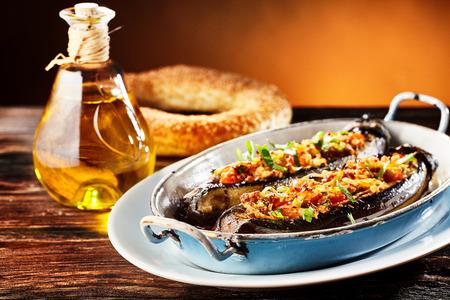 poblíž: Delicious plněný čerstvý brinjal, lilek nebo lilek se slanou pikantní vegetariánskou náplní podávanou v kovové misce s preclíky a olivovým olejem Reklamní fotografie