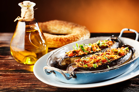 Delicious stuffed fresh brinjal, aubergine or eggplant with a savory spicy veggie stuffing served in a metal dish with a pretzel and olive oil