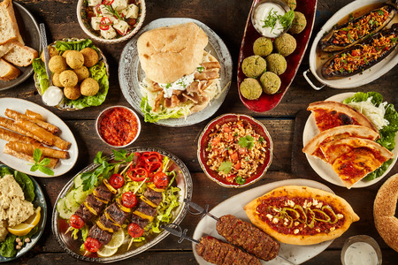 Top down view on freshly prepared delicious varieties of Mediterranean dishes on wooden table