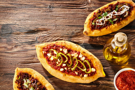restaurant dining: Top down view of Turkish Pizza with cheese and pepper toppings beside bottle of olive oil and red sauce