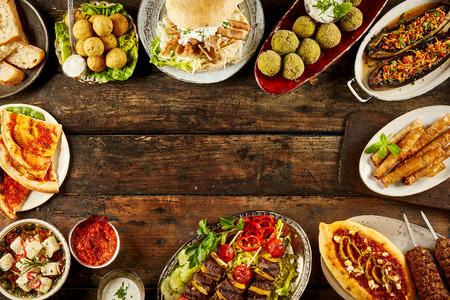 Grens van mediterrane gerechten en brood op tafel. Kopieer de ruimte in het midden over donker houten oppervlak.