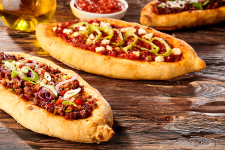 ovenbaked: Savory oven-baked Turkish pide pizza bread with sauce and oil on old wooden brown table