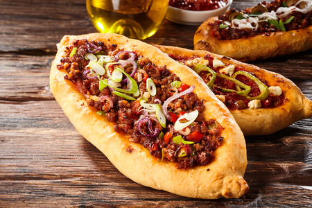 Freshly baked loaves of Turkish pizza bread with meat, peppers and spices on old wooden table