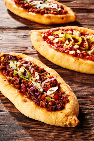 Close up on trio of freshly baked pizza loaves covered with peppers and onion on old wooden table
