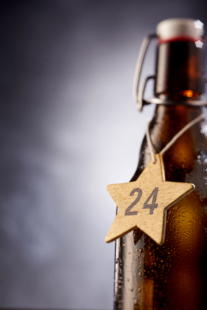 Star shaped tag with 24 December number around bottle in front of gray gradient background with copy space