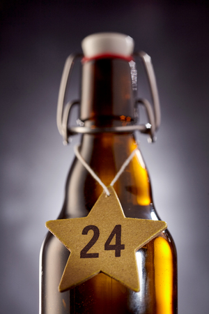 Close up view on number 24 xmas beer in middle of star shape tag around glass bottle bottle used for aging beverages